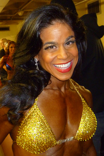 Tara Marie smiling in gold swimsuit